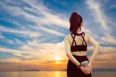 Concetto di salute, di sport e di allenamento - giovane ente asiatico di riscaldamento della donna prima del quotidiano di allena fotografia stock libera da diritti