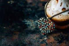 Concetto di San Valentino - pendente dei gioielli del cuore su fondo nero Immagini Stock