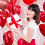 Concetto di San Valentino - sognare il contenitore di regalo della tenuta della donna sopra il fondo rosso dei palloni immagine stock libera da diritti