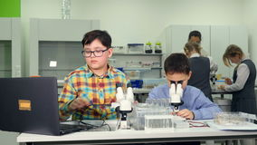 Concetto di scienza della scuola Gli studenti della scuola elementare che fanno una scienza sperimentano con le lumache archivi video