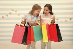 Concetto di sconto Ragazze sveglie dei bambini tenere i sacchetti della spesa Stagione di compera di sconto Grande tempo di spesa fotografia stock libera da diritti