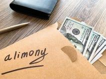 Concetto di separazione e di divorzio Assegno alimentare scritto su una busta con i dollari immagine stock
