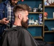 Concetto di servizio dell'acconciatura Il cliente barbuto dei pantaloni a vita bassa ha ottenuto l'acconciatura Il barbiere con i fotografia stock