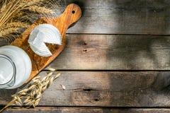 Concetto di Shavout - grani, latte e formaggio su fondo di legno immagini stock
