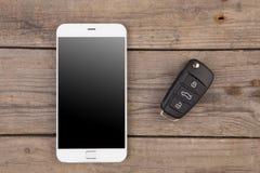 Concetto di sicurezza dell'automobile - chiave con controllo e lo smartphone dell'allarme a distanza Fotografia Stock Libera da Diritti