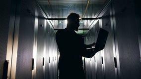 Concetto di sicurezza della rete dell'IT L'ingegnere maschio retroilluminato sta lavorando con un computer portatile archivi video