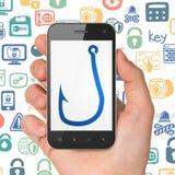 Concetto di sicurezza: Passi la tenuta dello Smartphone con il gancio di pesca su esposizione Immagini Stock