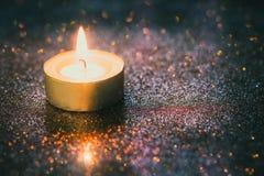 Concetto di speranza e di preghiera Retro luce della candela con effetto della luce immagine stock