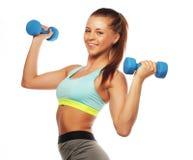 Concetto di sport, di forma fisica e della gente: Donna nell'uso delle apparecchiature di sport con i pesi della mano isolati su  immagine stock