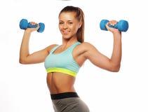Concetto di sport, di forma fisica e della gente: Donna nell'uso delle apparecchiature di sport con i pesi della mano isolati su  fotografia stock