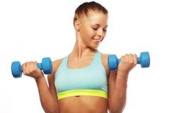 Concetto di sport, di forma fisica e della gente: Donna nell'uso delle apparecchiature di sport con i pesi della mano isolati su  fotografie stock