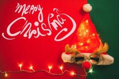 Concetto di stagione di saluto Cappello di Santa Claus con la luce e i glas della stella Fotografia Stock Libera da Diritti