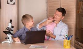 Concetto di stile di vita della famiglia Ragazzo sorridente che fa compito facendo uso del lapto immagine stock
