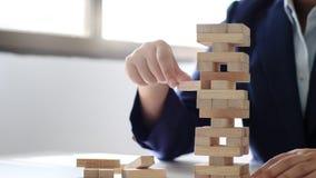 Concetto di strategia e di rischio, donna di affari con il blocco di legno per la sfida immagine stock