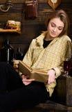 Concetto di studio Studio della studentessa con il libro in casa della guardiacaccia La ragazza in attrezzatura casuale si siede  Fotografia Stock
