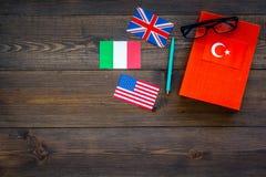Concetto di studio di lingua I manuali o i dizionari della lingua straniera vicino alle bandiere sulla vista superiore del backgr Immagini Stock Libere da Diritti