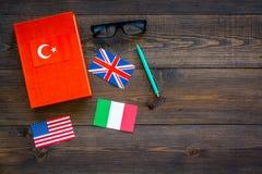 Concetto di studio di lingua I manuali o i dizionari della lingua straniera vicino alle bandiere sulla vista superiore del backgr Fotografie Stock