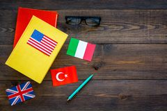 Concetto di studio di lingua I manuali o i dizionari della lingua straniera vicino alle bandiere sulla vista superiore del backgr Fotografia Stock