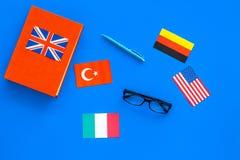 Concetto di studio di lingua Manuali o dizionari della lingua straniera vicino alle bandiere sulla vista superiore del backgrond  Immagine Stock Libera da Diritti