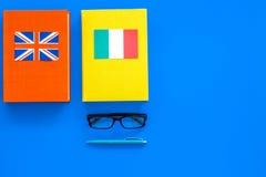 Concetto di studio di lingua Manuali o dizionari della lingua straniera vicino alle bandiere sullo spazio blu della copia di vist Fotografia Stock