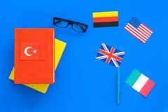 Concetto di studio di lingua Manuali o dizionari della lingua straniera vicino alle bandiere sullo spazio blu della copia di vist Immagine Stock