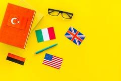 Concetto di studio di lingua Manuali o dizionari della lingua straniera vicino alle bandiere sullo spazio giallo della copia di v Fotografie Stock
