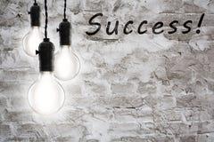Concetto di successo - lampadine incandescenti d'annata sul fondo della parete Fotografia Stock Libera da Diritti
