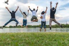 Concetto di successo di lavoro di squadra con il gruppo di amici di salto nel parco pubblico fotografia stock