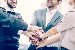 Concetto di successo nell'affare: gruppo amichevole di affari che sta in un cerchio e che unisce insieme le sue mani fotografia stock