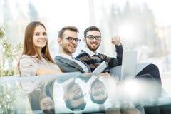 Concetto di successo nell'affare - un gruppo professionale di affari che si siede vicino alla tavola trasparente su un fondo legg Fotografia Stock