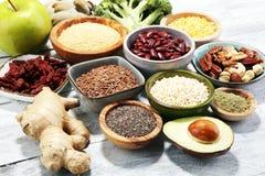 Concetto di Superfood sulla tavola bianca con l'avocado, il goji ed i dadi e immagine stock libera da diritti