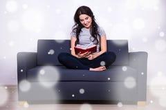 Concetto di svago di inverno - donna che si siede sul sofà e sul libro di lettura Fotografia Stock