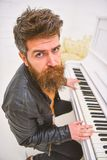 Concetto di talento del musicista L'uomo in bomber si siede vicino allo strumento musicale del piano nell'interno bianco su fondo fotografia stock