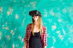 Concetto di tecnologia, di realtà virtuale, di spettacolo e della gente - donna con la cuffia avricolare del vr che gioca gioco Immagine Stock