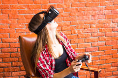 Concetto di tecnologia, di realtà virtuale, di spettacolo e della gente - donna con la cuffia avricolare del vr che gioca gioco Fotografia Stock
