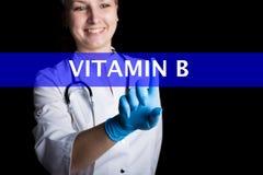 Concetto di tecnologia e di Internet medico femminile sorridente preme un dito su uno schermo virtuale vitamina b scritta sulla a Immagini Stock