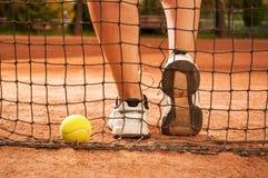 Concetto di tennis con i piedi della palla, del reticolato e della donna Immagine Stock
