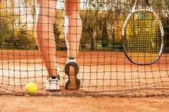 Concetto di tennis con le gambe della palla, del reticolato, della racchetta e della donna Fotografia Stock Libera da Diritti