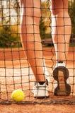 Concetto di tennis con le gambe della palla, del reticolato e della donna Fotografia Stock