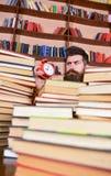 Concetto di termine Uomo sul fronte rigoroso che esamina orologio, scaffali per libri su fondo Insegnante o studente con lo studi Fotografia Stock