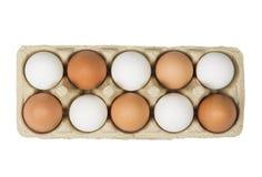 Concetto di tolleranza Uova di Brown fra le uova bianche in scatola isolata su fondo bianco Vista superiore Fotografie Stock