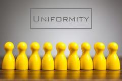Concetto di uniformità con le figurine del pegno sulla tavola, immagini stock libere da diritti