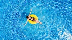 Concetto di vacanza Punto di vista superiore della giovane donna esile in bikini sull'anello gonfiabile dell'aria gialla nella gr fotografie stock libere da diritti