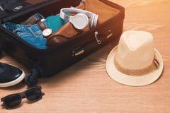 Concetto di vacanze e di viaggio Apra la borsa del ` s del viaggiatore con abbigliamento Fotografia Stock