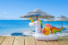 Concetto di vacanze estive con il galleggiante dello stagno dell'unicorno e del succo d'arancia sopra il fondo della spiaggia del fotografie stock
