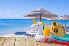 Concetto di vacanze estive con succo d'arancia, gli accessori della spiaggia ed il galleggiante dello stagno dell'unicorno sopra  immagini stock libere da diritti