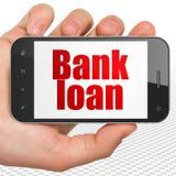 Concetto di valuta: Passi la tenuta dello Smartphone con il prestito bancario su esposizione Fotografia Stock Libera da Diritti