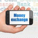 Concetto di valuta: Passi la tenuta dello Smartphone con lo scambio di soldi su esposizione Fotografie Stock Libere da Diritti