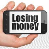 Concetto di valuta: Passi la tenuta dello Smartphone con soldi perdenti su esposizione Fotografia Stock Libera da Diritti