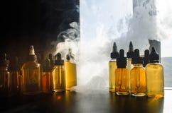 Concetto di Vape Nuvole di fumo e bottiglie liquide del vape sulla finestra con luce solare su fondo Effetti della luce Utile com Fotografie Stock